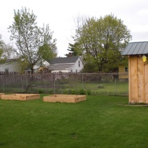 Spring 2009. With the shed complete, a few simple raised beds are added. Eventually I would like to encase them with stone. I spaced them with this in mind.