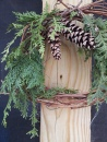A simple wreath made with grapevines, cedar boughs and pine cones.